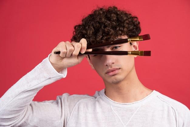 Jonge mannelijke kunstenaar poseren met penselen.