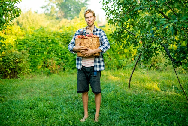 Jonge mannelijke landbouwer die een mand met verzamelde oogstvruchten en groenten in een tuinlandbouwbedrijf houdt