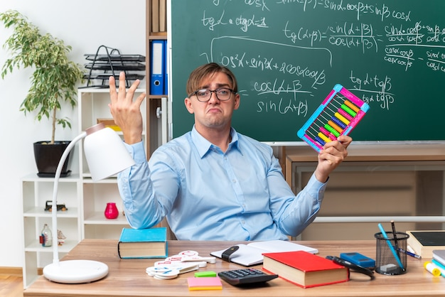 Jonge mannelijke leraar bril met rekeningen kijken verward voorbereiding les zitten op school bureau met boeken en notities voor bord in de klas