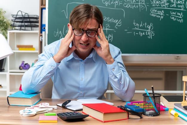 Jonge mannelijke leraar die een bril draagt, gestrest en nerveus zit aan de schoolbank met boeken en notities voor het bord in de klas