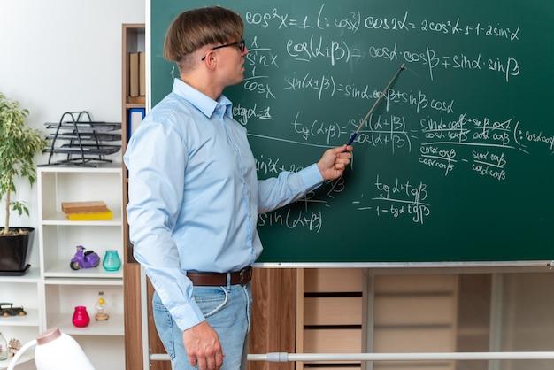 Jonge mannelijke leraar die een bril draagt met een aanwijzer die de les gelukkig en positief glimlachend uitlegt die in de buurt van het bord staat met wiskundige formules in de klas