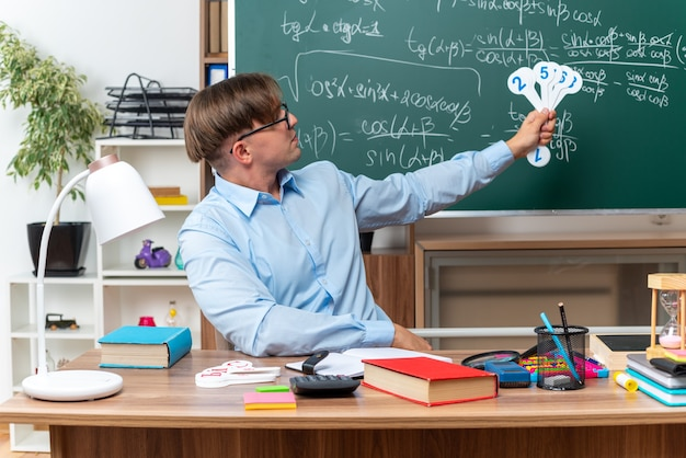 Jonge mannelijke leraar die een bril draagt met nummerplaten die les uitleggen glimlachend zelfverzekerd zittend aan schoolbureau met boeken en notities voor schoolbord in de klas