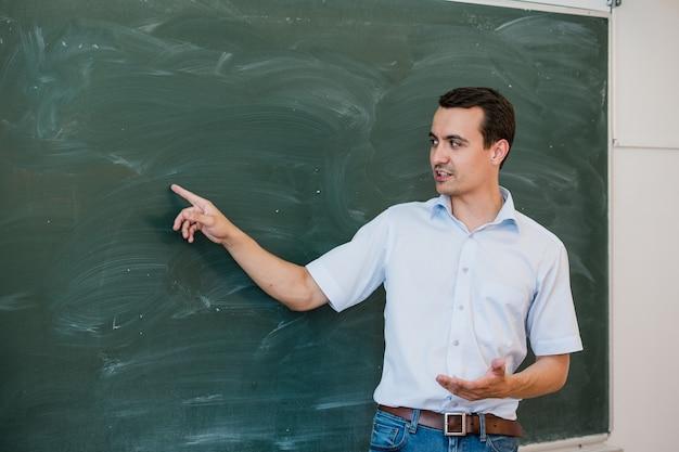 Jonge mannelijke leraar die op leeg bord en het spreken richt