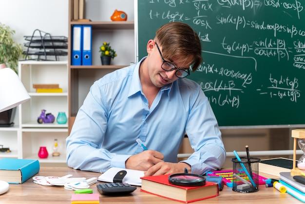 Jonge mannelijke leraar met een bril die aan de schoolbank zit met boeken en notities die voor het bord in de klas schrijven