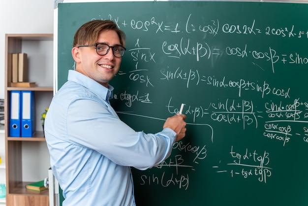 Jonge mannelijke leraar met een bril die de les gelukkig en positief glimlachend uitlegt terwijl hij in de buurt van het bord staat met wiskundige formules in de klas