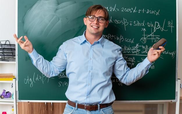 Jonge mannelijke leraar met een bril die een spons vasthoudt die zelfverzekerd glimlacht en in de buurt van het bord staat met wiskundige formules in de klas