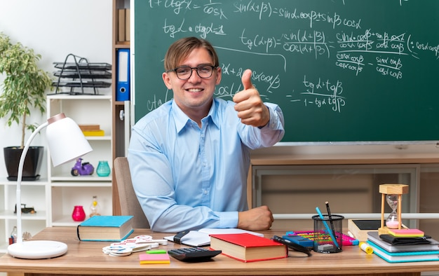 Jonge mannelijke leraar met een bril die er glimlachend zelfverzekerd uitziet en duimen opsteekt terwijl hij aan de schoolbank zit met boeken en notities voor het bord in de klas