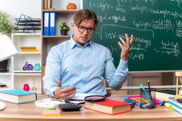 Jonge mannelijke leraar met een bril die er verward en teleurgesteld uitziet terwijl hij aan de schoolbank zit met boeken en aantekeningen voor het bord in de klas