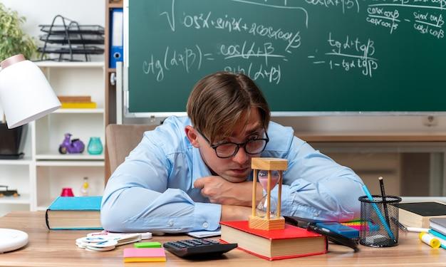 Jonge mannelijke leraar met een bril die naar zandloper kijkt, moe en verveeld zit aan de schoolbank met boeken en notities voor het bord in de klas