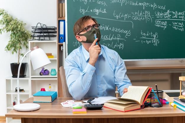 Jonge mannelijke leraar met een bril en een gezichtsbeschermend masker die verbaasd opkijkt terwijl hij aan de schoolbank zit met boeken en notities voor het bord in de klas