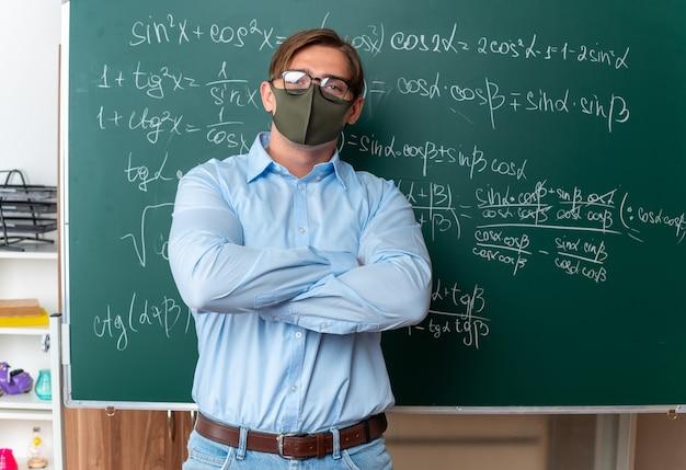 Jonge mannelijke leraar met een bril in een gezichtsbeschermend masker die in de buurt van het bord staat met wiskundige formules die er zelfverzekerd uitziet met gekruiste armen in de klas