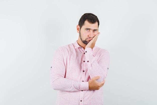 Jonge mannelijke leunende wang op opgeheven palm in roze overhemd en het kijken vermoeid