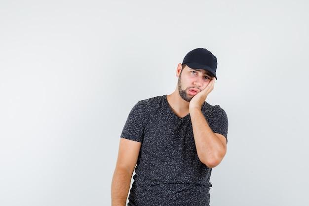 Jonge mannelijke leunende wang op palm in t-shirt en pet en kijkt uitgeput