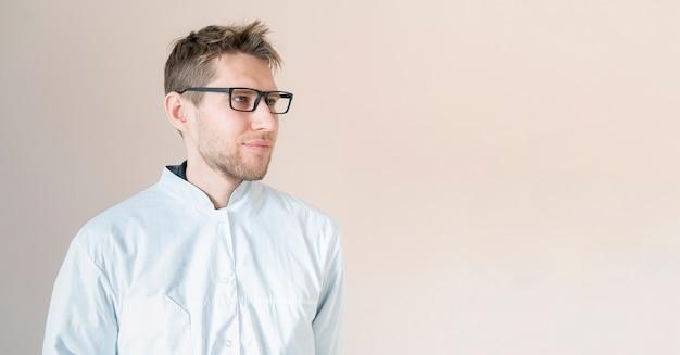 Jonge mannelijke medische werker, arts in wit uniform, zelfverzekerde arts Premium Foto