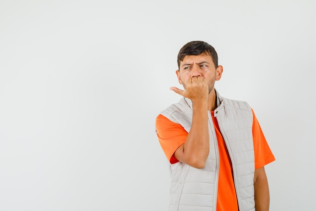 Jonge mannelijke nagels bijten terwijl opzij in t-shirt, jasje kijken en onrustig kijken. vooraanzicht.