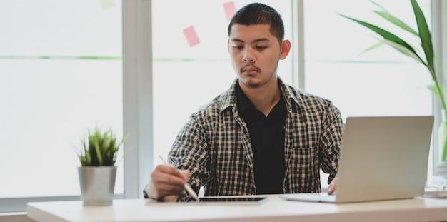 Jonge mannelijke ontwerper die aan zijn project werkt terwijl het gebruiken van laptop