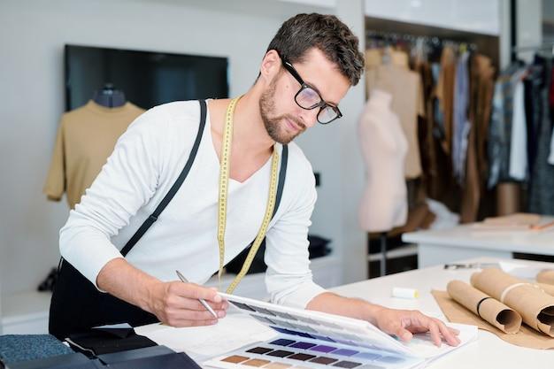 Jonge mannelijke ontwerper van mode kijken naar textielmonsters in de catalogus en geschikte kiezen voor nieuwe collectie