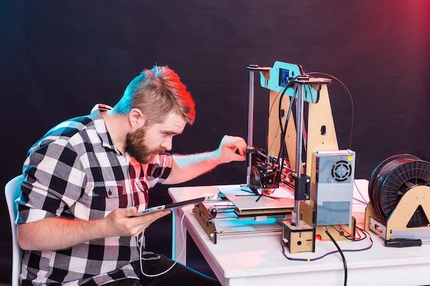 Jonge mannelijke ontwerperingenieur die een printer in het laboratorium gebruikt en een productprototype, technologie en innovatieconcept bestudeert.
