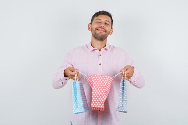 Jonge mannelijke opening papieren zak in overhemd en op zoek blij, vooraanzicht.