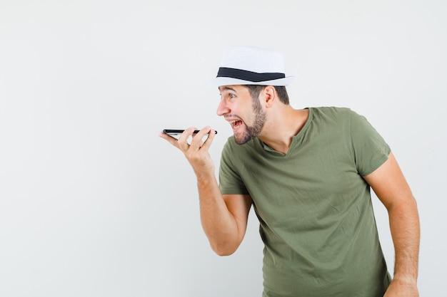 Jonge mannelijke opname spraakbericht op mobiele telefoon in groen t-shirt en hoed en ziet er energiek uit