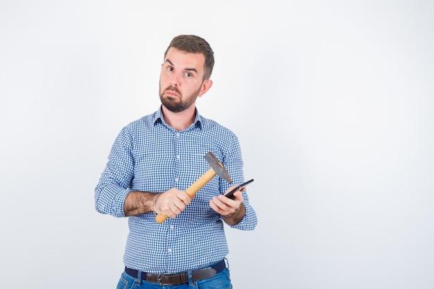 Jonge mannelijke opvallende mobiele telefoon met een hamer in shirt, spijkerbroek en op zoek aarzelend, vooraanzicht.