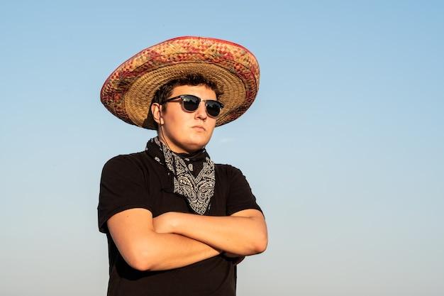Jonge mannelijke persoon in sombrero en zonnebril op heldere hemelachtergrond. mexico onafhankelijkheids feestelijk concept van man met nationale mexicaanse hoed en westerse stijl bandana