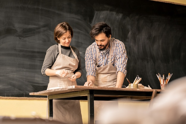 Jonge mannelijke pottenbakker in schort toont zijn vrouwelijke collega een van de nieuwe items terwijl hij over het ontwerp van aardewerk werkt