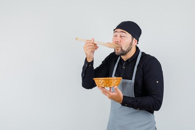 Jonge mannelijke proeverij maaltijd terwijl rieten mand in overhemd, schort en verrukt, vooraanzicht kijken.