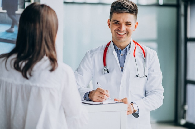 Jonge mannelijke psysician met patiënt bij het ziekenhuis
