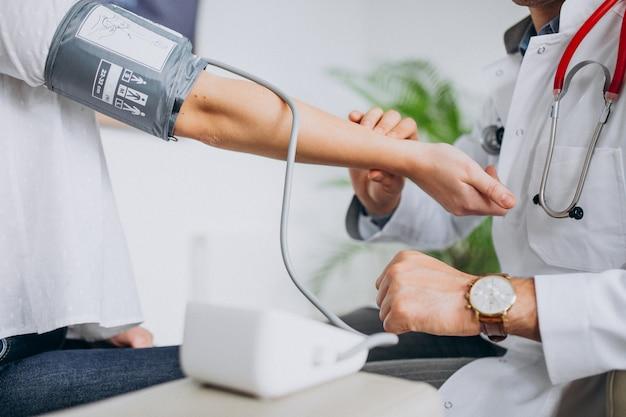 Jonge mannelijke psysician met patiënt die bloeddruk meet