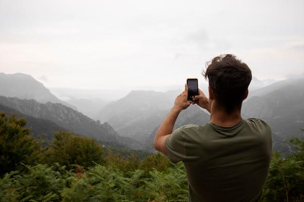 Jonge mannelijke reiziger die een foto van de bergen maakt met zijn smartphone