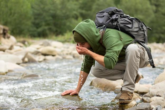Jonge mannelijke reiziger die geniet van een landelijke omgeving