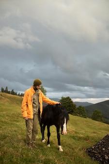 Jonge mannelijke reiziger die naast een paard staat