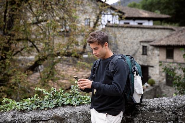 Jonge mannelijke reiziger die zijn smartphone controleert