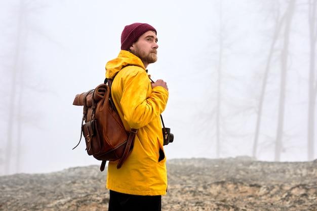 Jonge mannelijke reiziger in gele jas en hoed met camera ontspannen buiten op mistig weer vakanties...