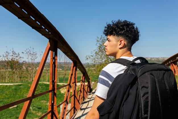 Jonge mannelijke reiziger met rugzak die op de brug door de rivier loopt