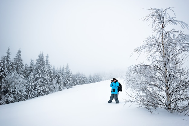 Jonge mannelijke reiziger met rugzak maakt foto's van een prachtige hoge besneeuwde dennenboom in een hoge sneeuwjacht tegen de achtergrond van mist op een ijzige winterdag