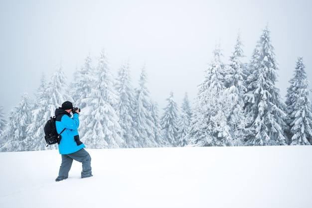 Jonge mannelijke reiziger met rugzak maakt foto's van een prachtige hoge besneeuwde dennenboom