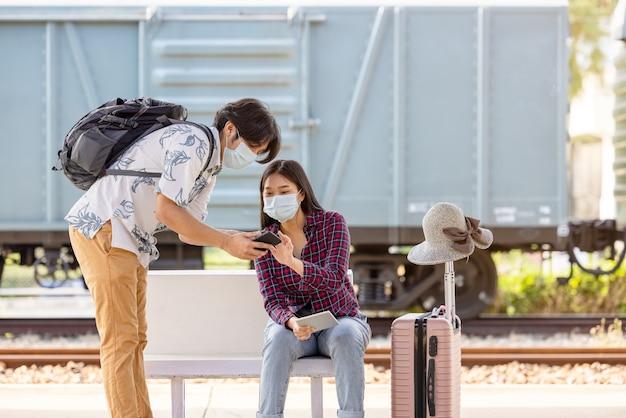 Jonge mannelijke reizigersrugzak met masker en mobiel in de hand die om hulp vraagt van een vrouw die zit en wijst op trappen in de metro, covid-afstand