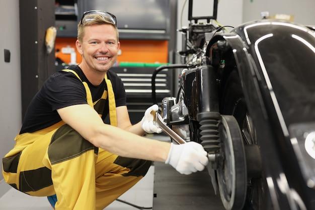 Jonge mannelijke reparateur in overall die motorfiets in werkplaats herstelt. reparatie van auto's en motorfietsen concept