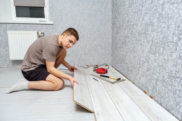Jonge mannelijke reparateur legt houten paneel van laminaatvloer binnenshuis op de knieën. laminaatvloer, kopie ruimte.