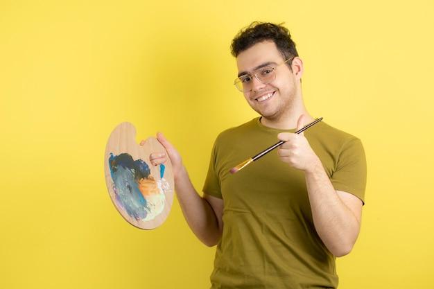Jonge mannelijke schilder met palet en penseel schilderen.