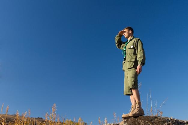 Jonge mannelijke scout staande op grote rots observeren het veld op het kampgebied op een blauwe hemelachtergrond.