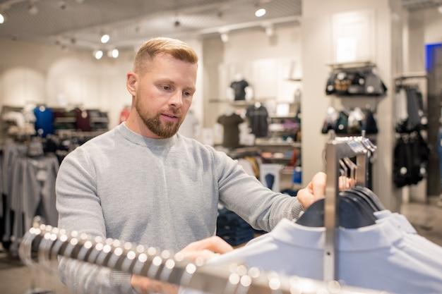 Jonge mannelijke shopper op zoek naar zijn maat terwijl hij door rek met rij shirts te koop staat en een nieuwe kiest