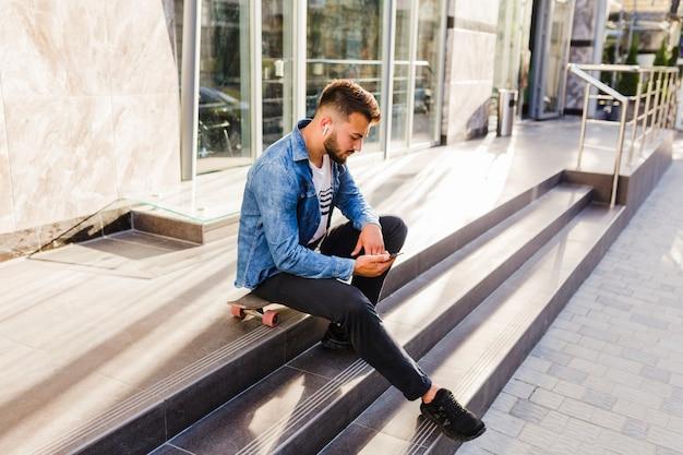 Jonge mannelijke skateboarder zittend op skateboard met behulp van mobiele telefoon