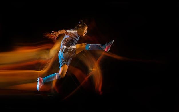 Jonge mannelijke sportieve modeltraining in actie schoppende bal