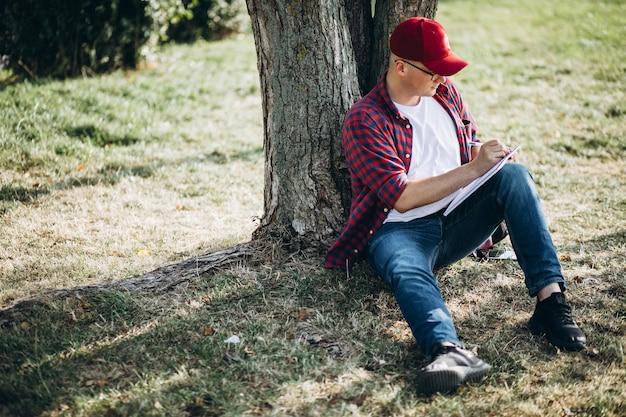 Jonge mannelijke student die aan een computer in park werkt