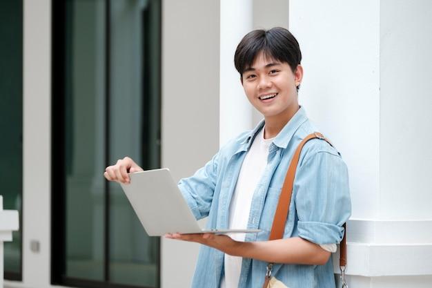 Jonge mannelijke student die aan laptop werkt