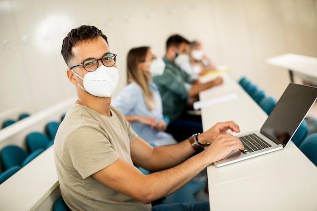 Jonge mannelijke student die gezichtsbeschermend medisch masker draagt voor virusbescherming in collegezaal