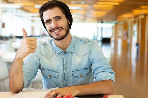 Jonge mannelijke student die in de bibliotheek bestudeert.